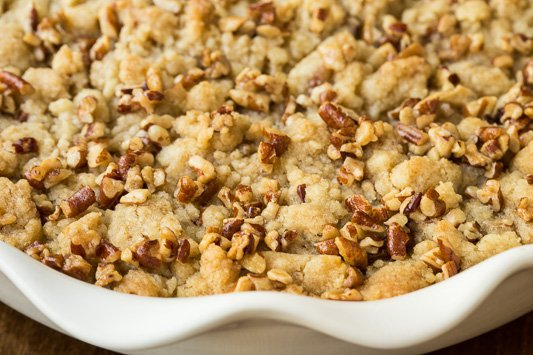 A closeup photo of a white serving dish filled with Easy Pumpkin Praline Cobbler.