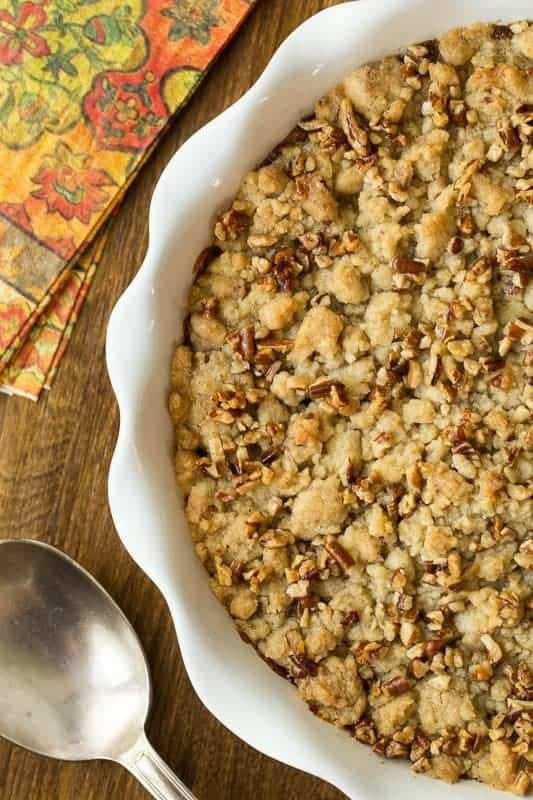 An overhead closeup photo of a serving dish of Easy Pumpkin Praline Cobbler with a serving spoon and fall napkins nearby on a wood table.