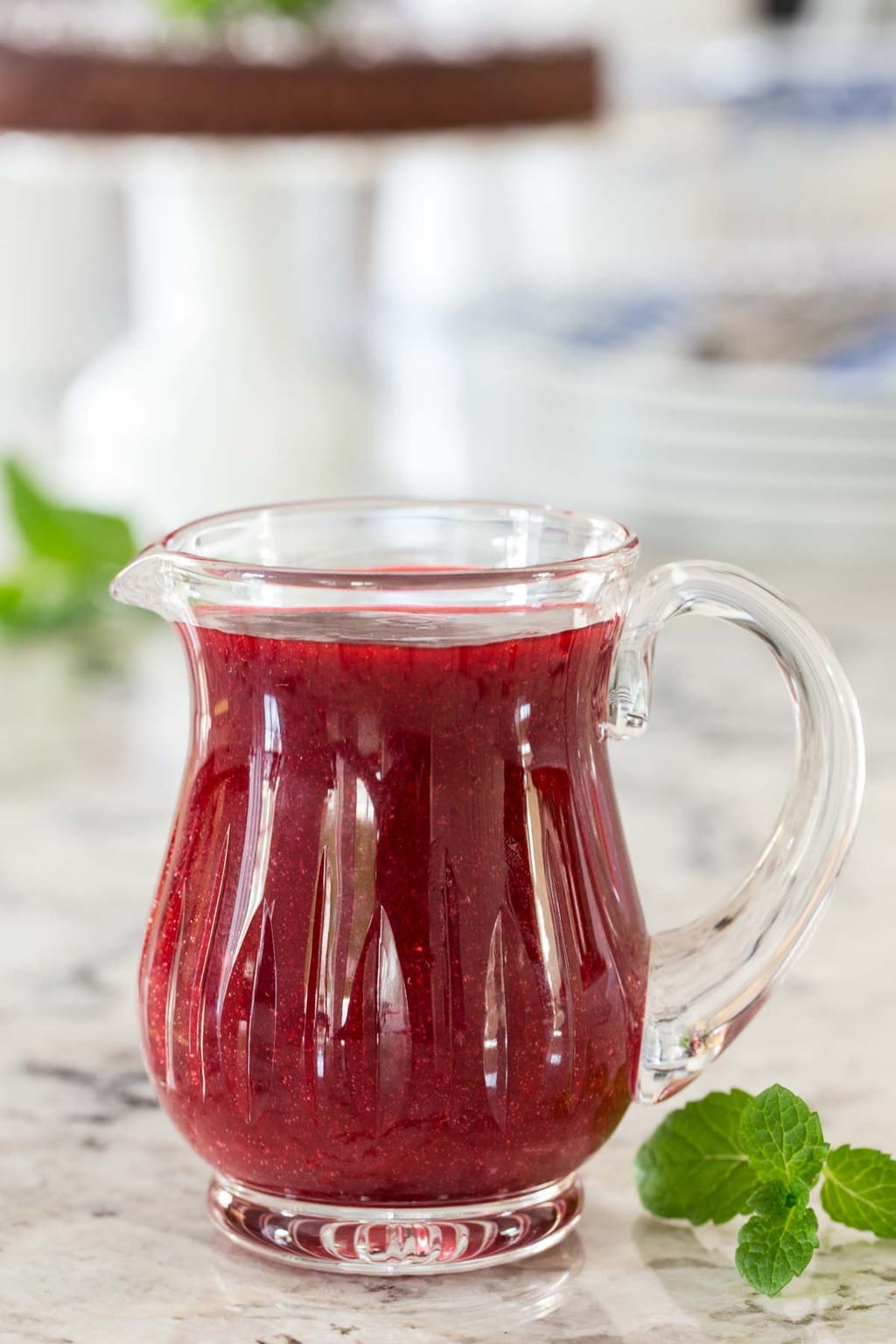Photo of a glass pitcher filled with Easy Raspberry Coulis on a granite kitchen countertop.
