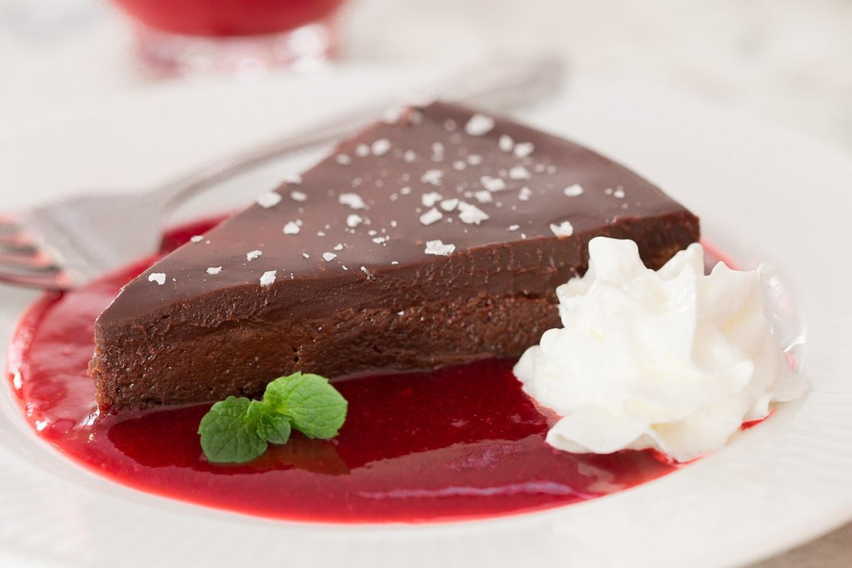 Photo of a chocolate dessert slice on a dessert plate in a pool of Ridiculously Easy Raspberry Coulis.