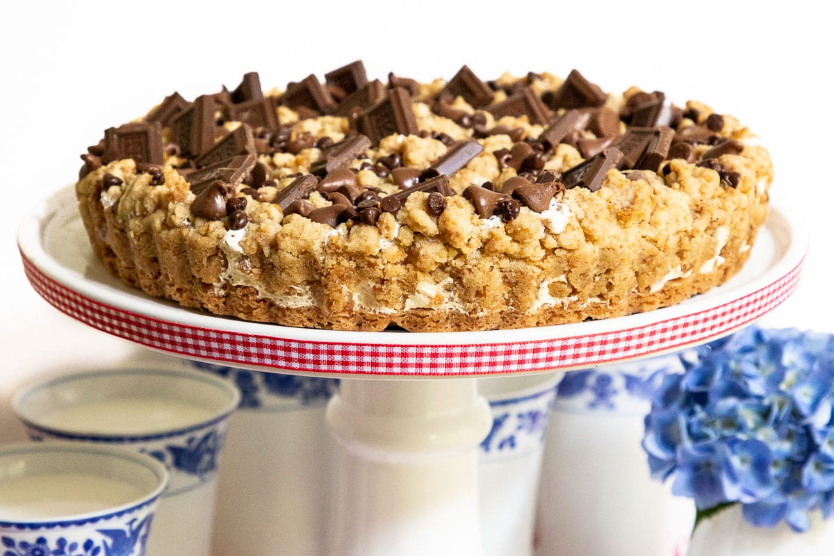 Vertical picture of S'mores Shortbread Tart on a white cake stand with blue and white glasses of milk underneath.