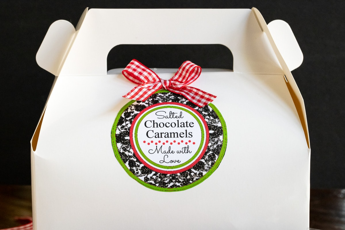 Horizontal photo of a white gift box with a custom Easy Salted Chocolate Caramels label and bow attached.