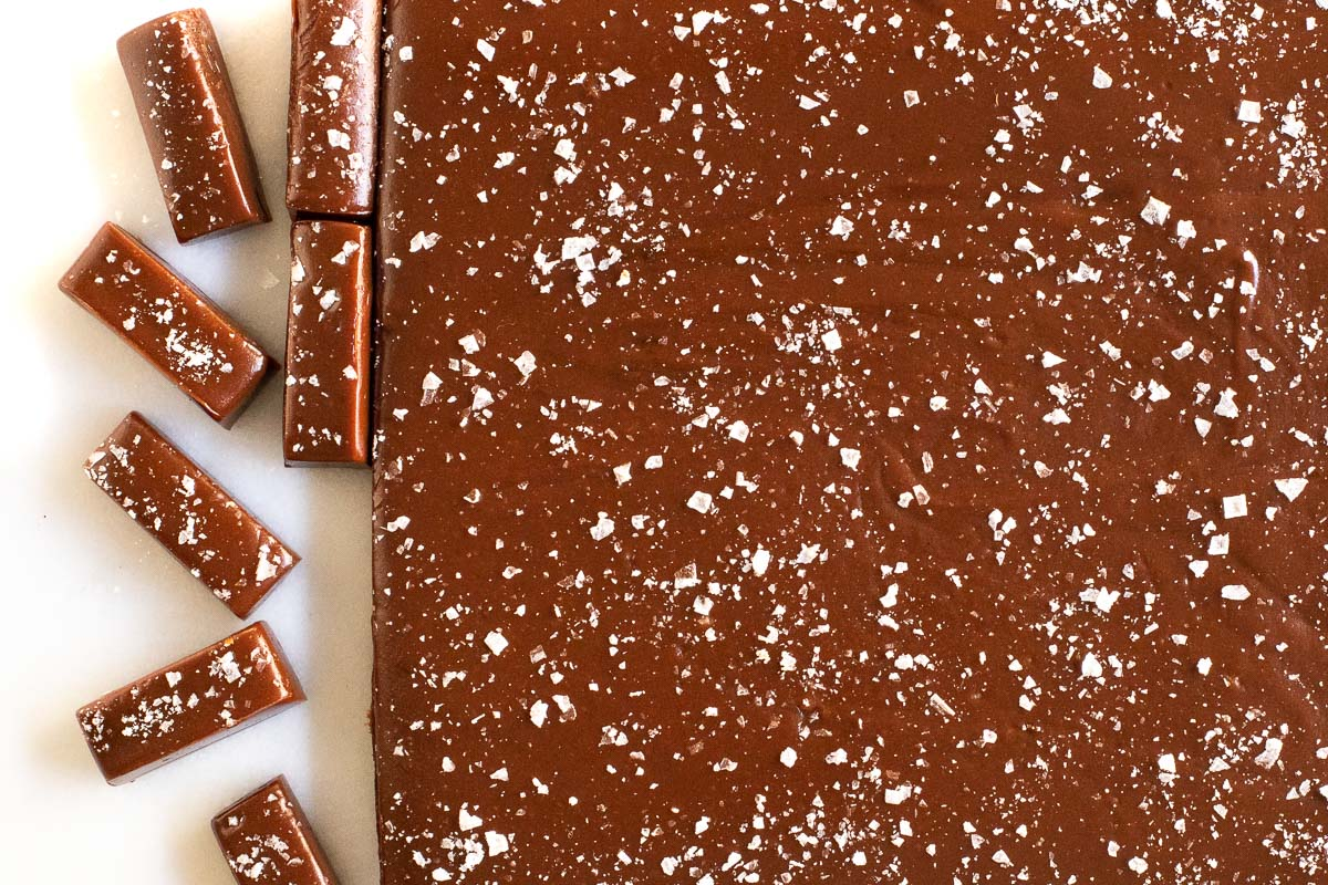 Overhead horizontal photo of a slab of Easy Salted Chocolate Caramels with two rows cut and ready for individual wrapping.