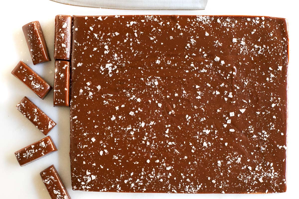 Horizontal overhead photo of a slab of Easy Salted Chocolate Caramels being cut into candy-sized pieces.