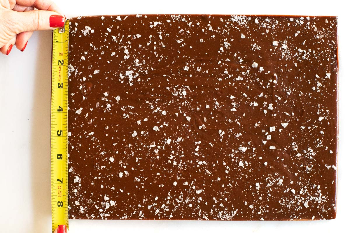 Overhead horizontal photo of a slab of Easy Salted Chocolate Caramels being measured for cutting into candy-size pieces.