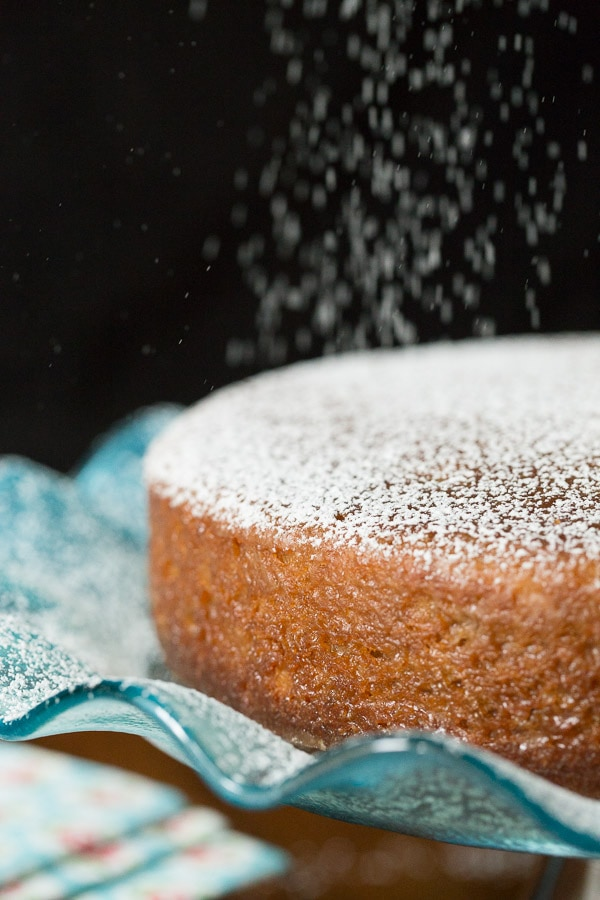 A vertical photo of an Easy Spice Cake on a turquoise cake plate being showered with powdered sugar.