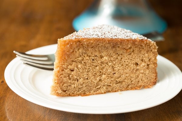 A slice of Easy Spice Cake on a white plate on a wood dining table.