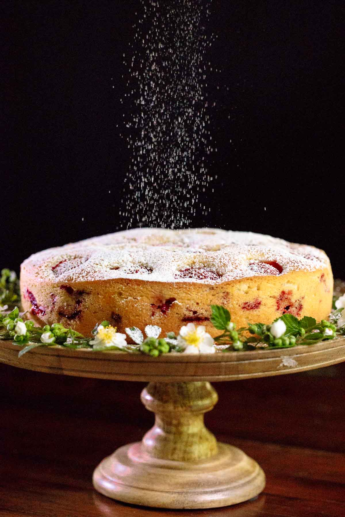 Photo of a Easy Fresh Strawberry Cake surrounded by fresh flowers on a wood cake stand being dusted with powdered sugar.