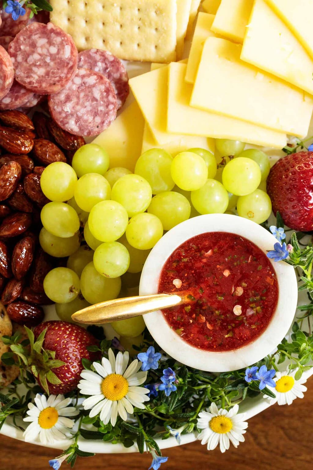 Overhead photo of an appetizer tray featuring Easy Strawberry Jalapeño Jam in a white dish surrounded by appetizer nibbles and decorative flowers.