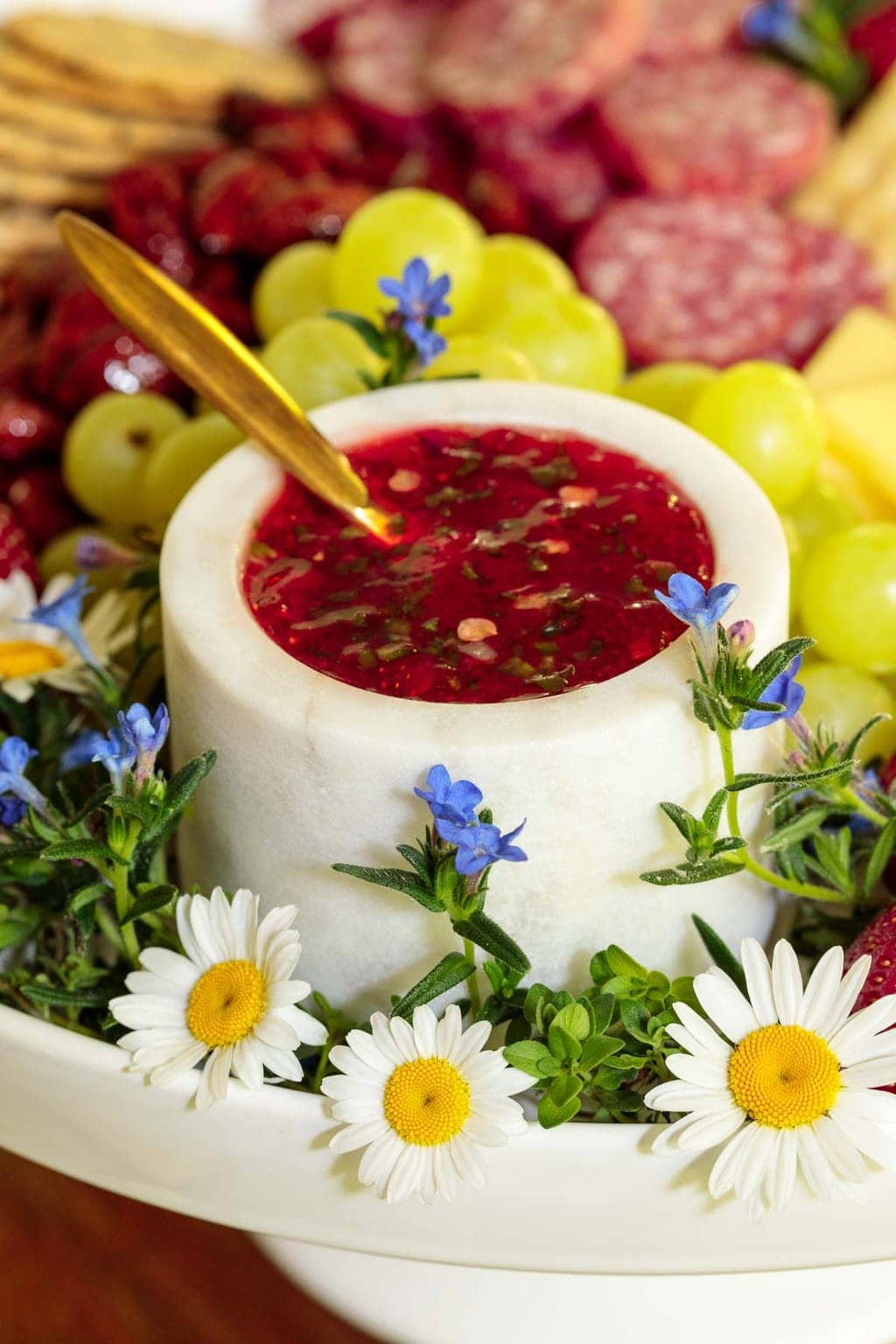 Vertical photo of a white marble bowl of Strawberry Jalapeño Jam on a charcuterie board with flowers in the foreground.