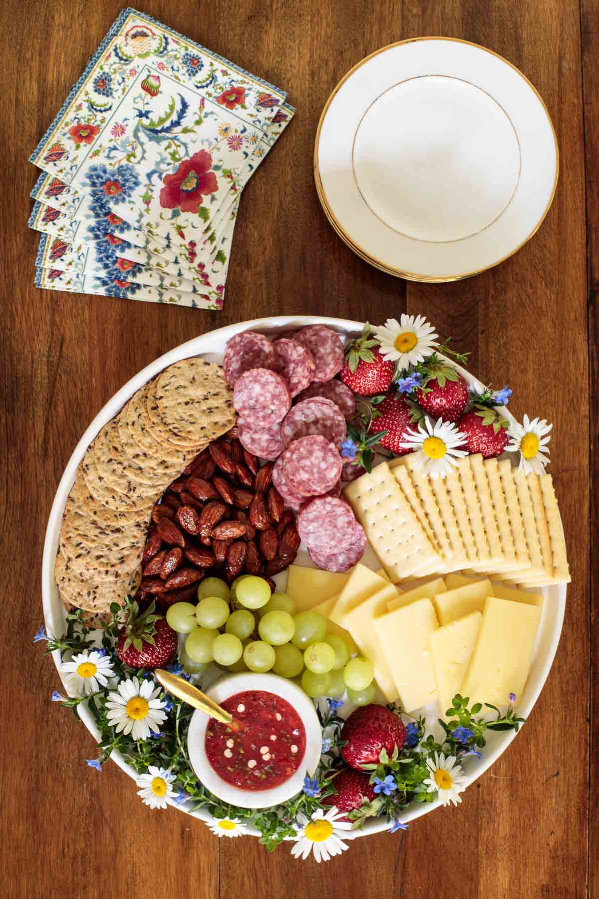 Overhead photo of an appetizer tray featuring Easy Strawberry Jalapeño Jam surrounded by appetizer snacks and decorative flowers on a wood table.