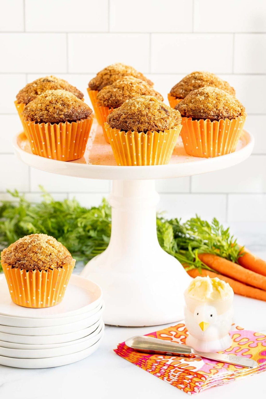 Vertical picture of carrot muffins on a white cake stand