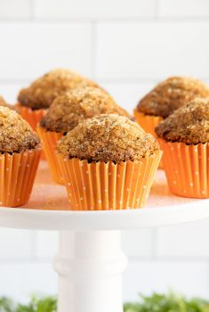 Vertical closeup photo of a batch of Sugar Top Carrot Muffins in orange cupcake liners on a white pedestal display platter.