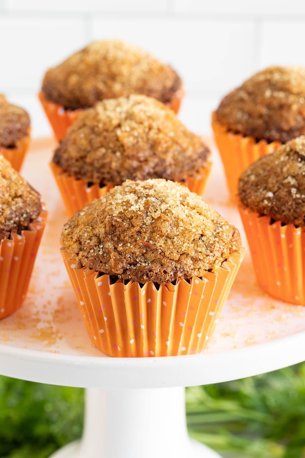 Vertical closeup photo of Sugar Top Carrot Muffins in orange cupcake liners on a white pedestal cake platter.