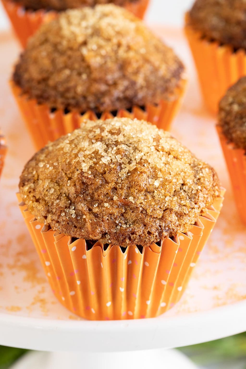Vertical closeup photo of a batch of Sugar Top Carrot Muffins sprinkled with sugar in orange cupcake liners.