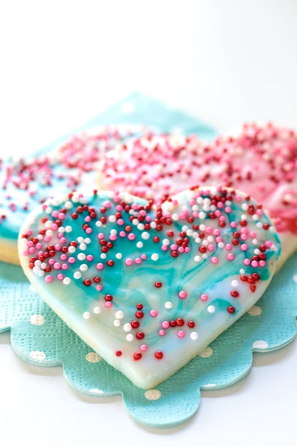 Closeup photo of a pile of Easy Valentine Cookies on a turquoise napkin.