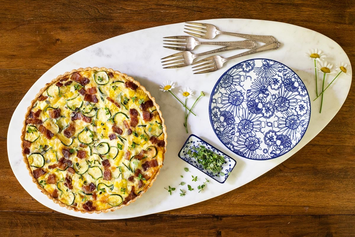 Horizontal overhead photo of an Easy Zucchini Quiche on an oval marble platter surrounded by spring daisies and thyme.