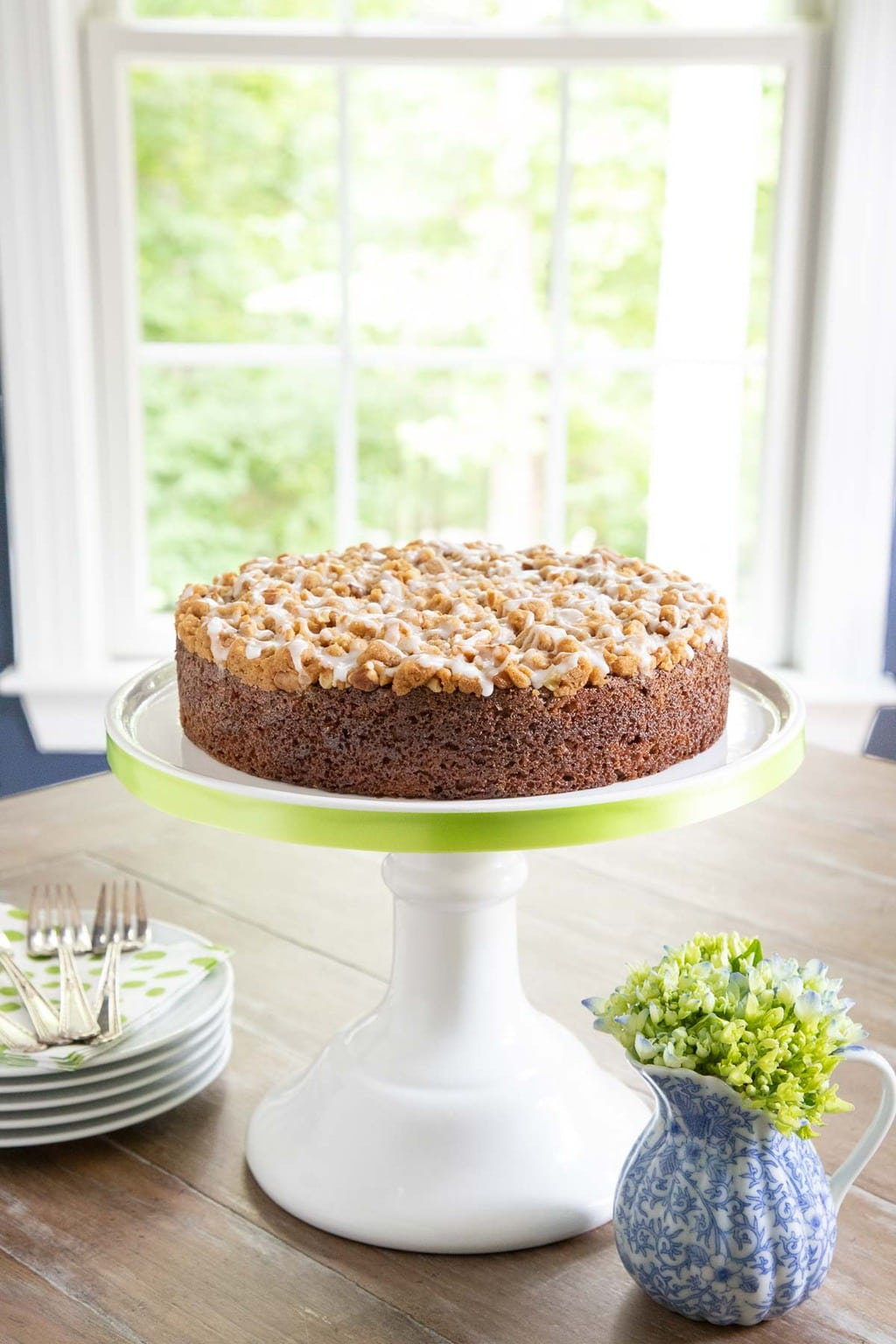 Vertical photo of an Easy Zucchini Crumb Cake in front of a window on a white pedestal cake stand trimmed in pale green ribbon.