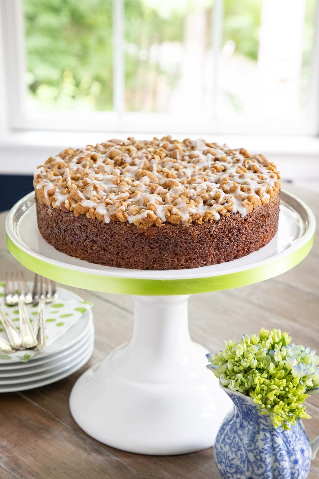 Vertical photo of an Easy Zucchini Crumb Cake on a white pedestal cake platter trimmed in pale green ribbon.