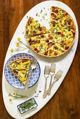 Overhead picture of zucchini summer quiche on a white platter