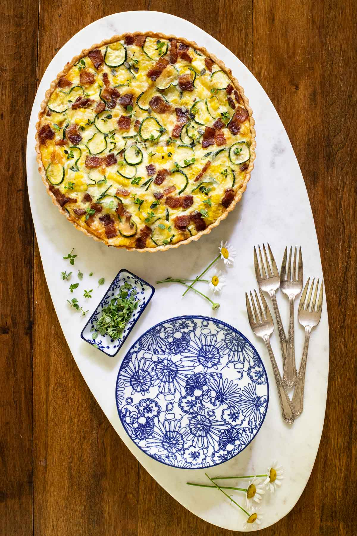 Overhead photo of a marble oval platter with an Easy Zucchini Summer Quiche and serving items.