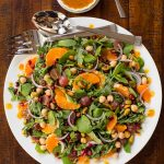 Overhead picture of Fall Salad with Pumpkin Maple Vinaigrette on a white platter with dressing