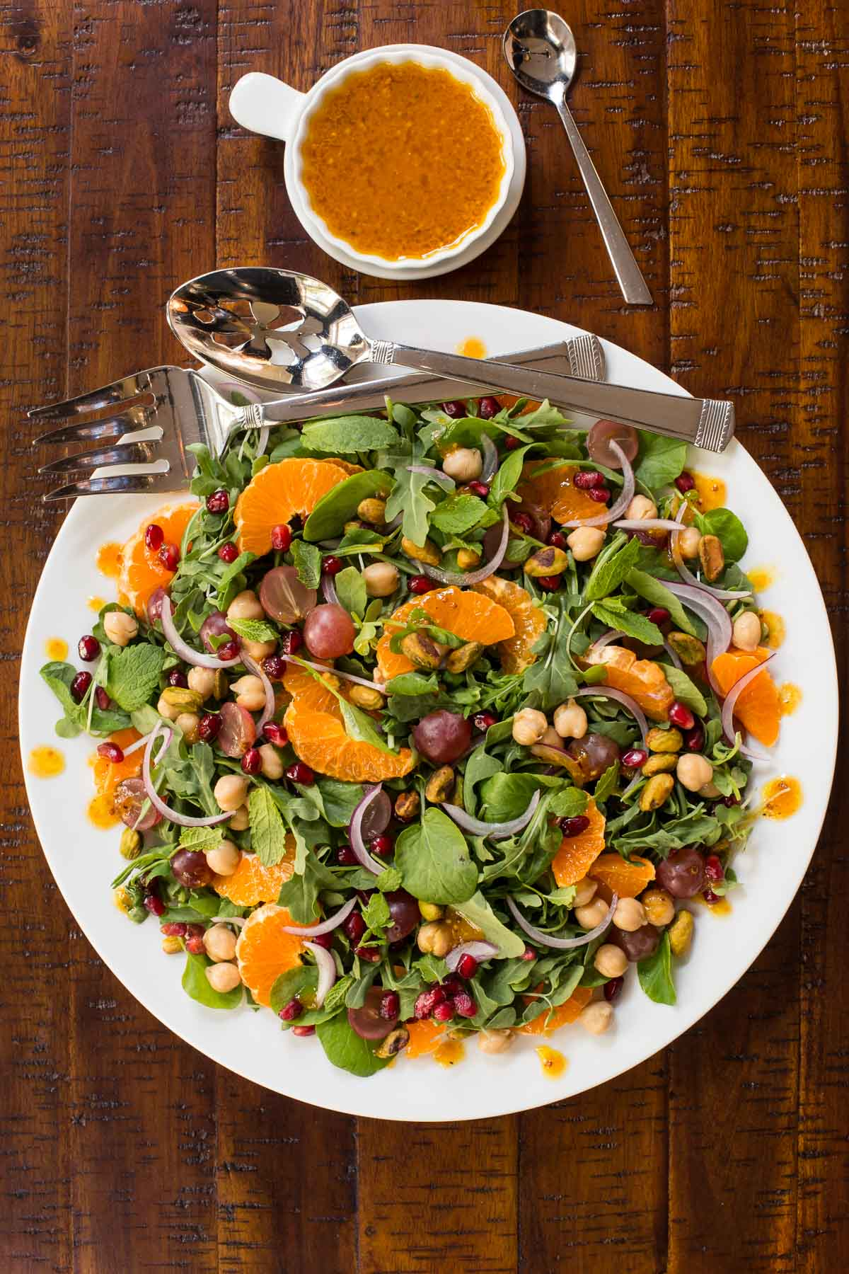 Overhead vertical photo of a Fall Salad with Pumpkin Maple Vinaigrette on a white serving platter with dressing in a cup on the side.