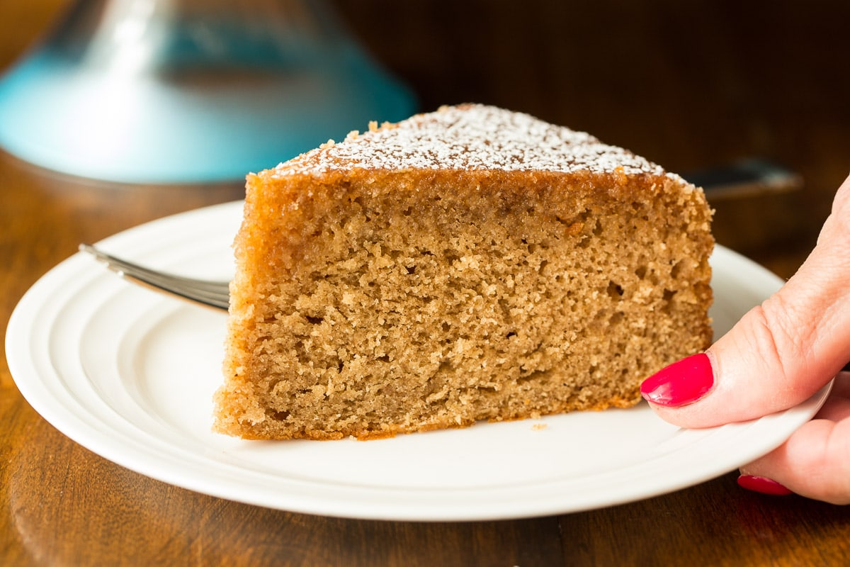 Closeup photo of a slice of spice cake with maple glaze held by person's hand on a white individual serving plate.