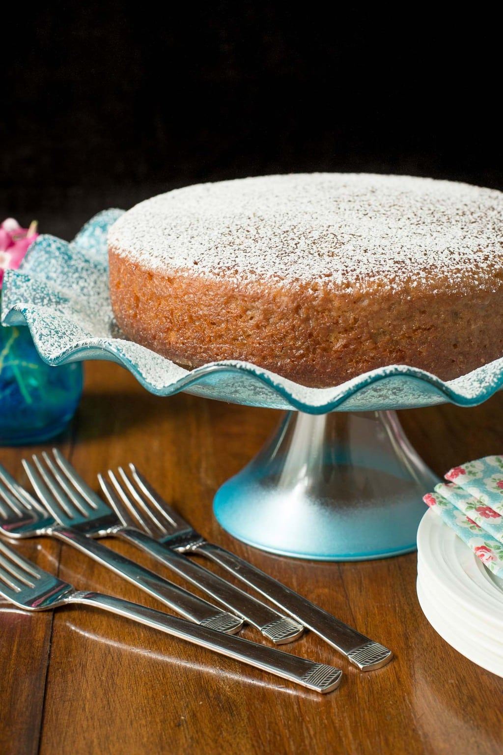 Vertical photo of a Fall Spice Cake with Maple Gaze dusted with powdered sugar on a turquoise glass cake stand.