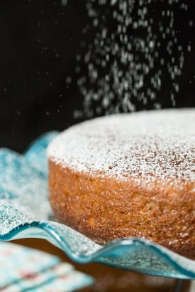 Photo of a Fall Spice Cake with Maple Glaze being sprinkled with powdered sugar.
