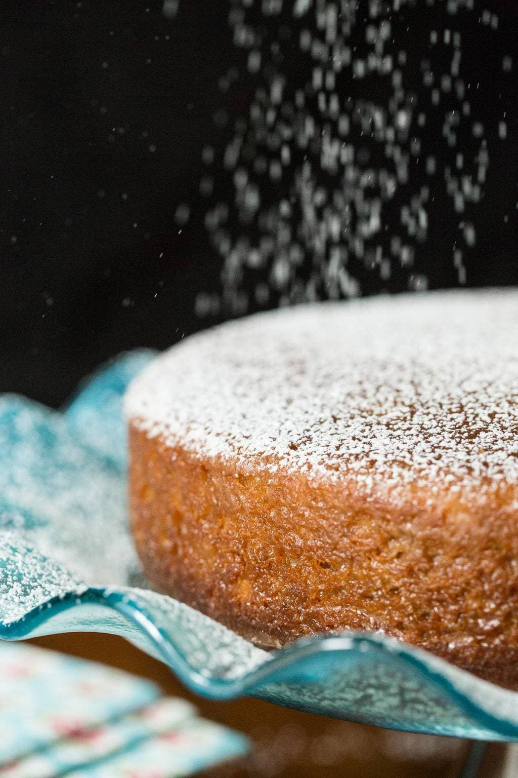 Closeup photo of powdered sugar being sprinkled on a Fall Spice Cake with Maple Glaze.