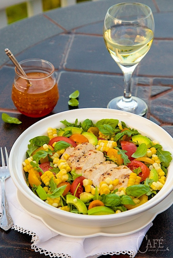 Vertical image of Farmer's Market Grilled Chicken Salad in a white shallow bowl with dressing and a glass of wine in the background..