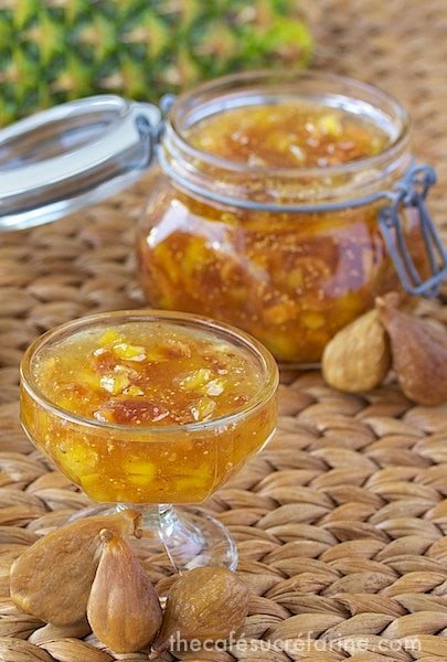 Photo of a glass dish of Fig and Fresh Pineapple Freezer Jam with a Ball jar of the jam in the background and dried figs in the foreground.