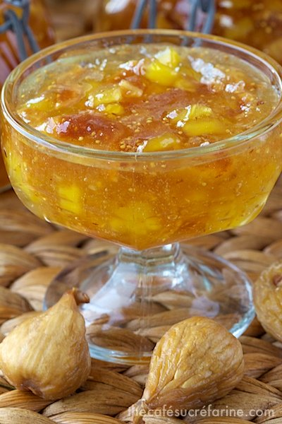 Closeup photo of a glass dish of Fig and Fresh Pineapple Freezer Jam, with dried figs in the foreground.