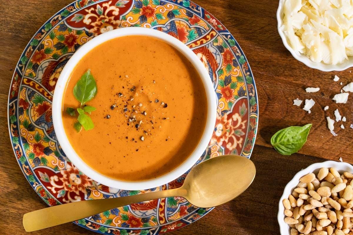 Overhead horizontal closeup photo of a bowl of Fire-Roasted Tomato Basil Soup on a wood table.