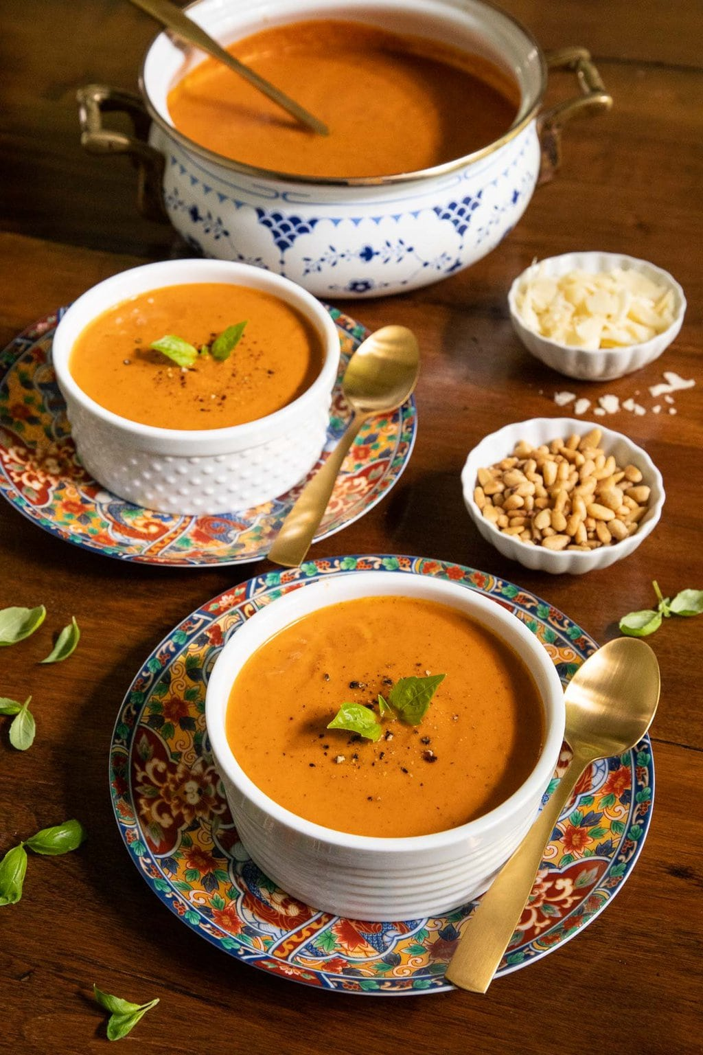 Vertical photo of bowls and a pot of Fire-Roasted Tomato Basil Soup on a wood table with small bowls of grated cheese and roasted pine nuts.
