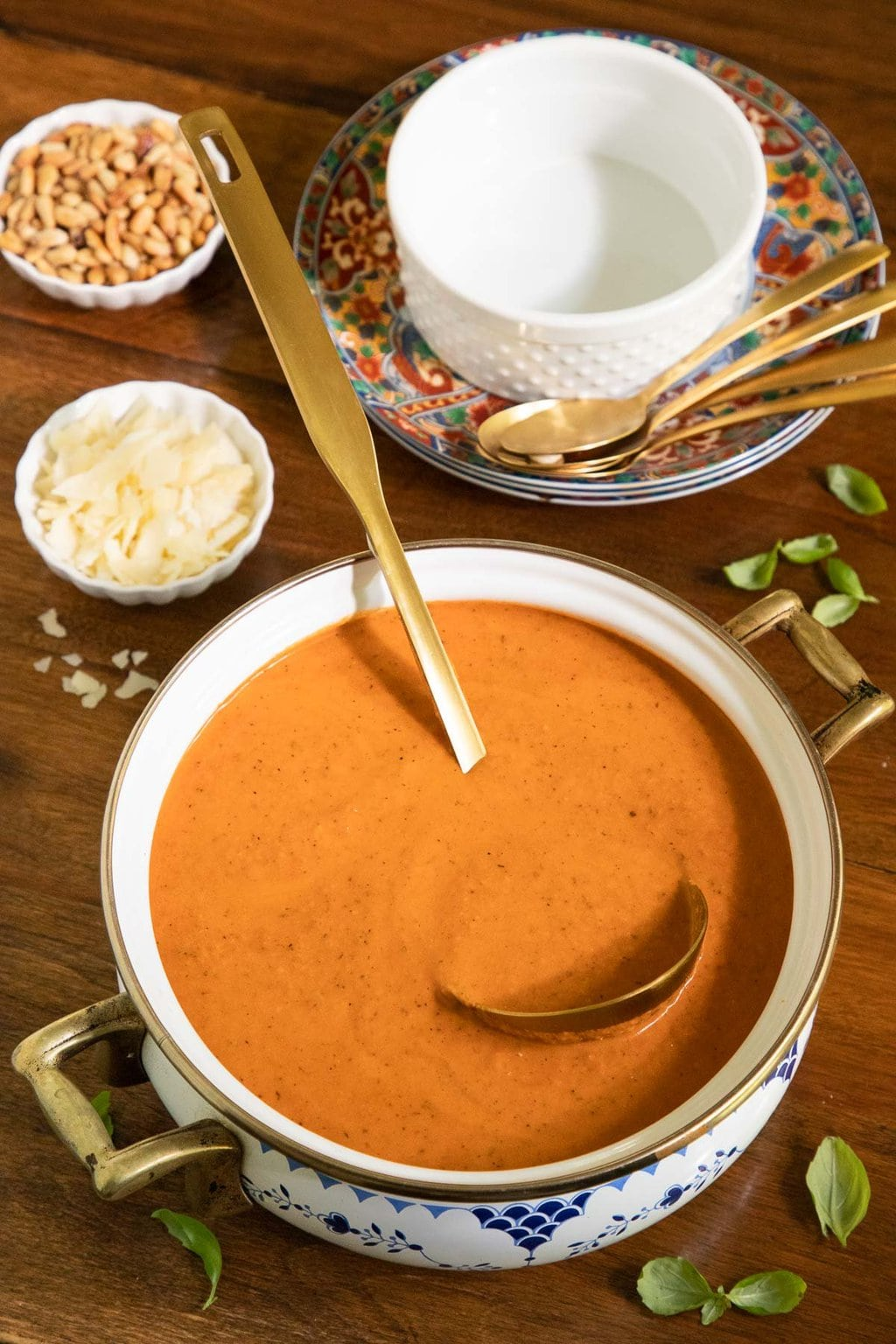 Vertical photo of a pot of Fire-Roasted Tomato Basil Soup on a wood table surrounded by bowls of roasted pine nuts, shaved cheese and fresh basil leaves.