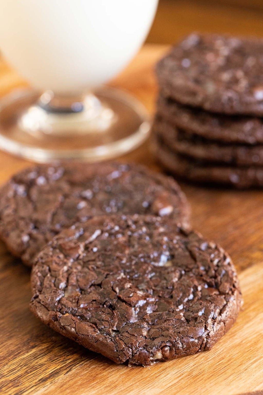 Vertical photo of a grouping of Flourless Toffee Chocolate Cookies on a wood platter.