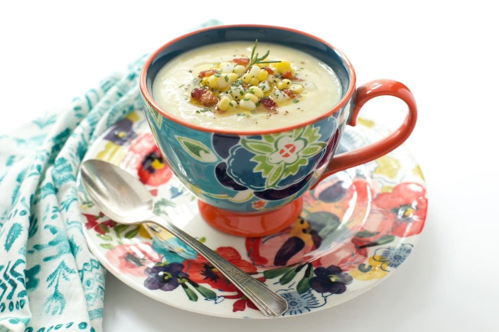 Photo of a cup of Fresh Corn Soup in a decorative Anthropology soup cup and saucer.