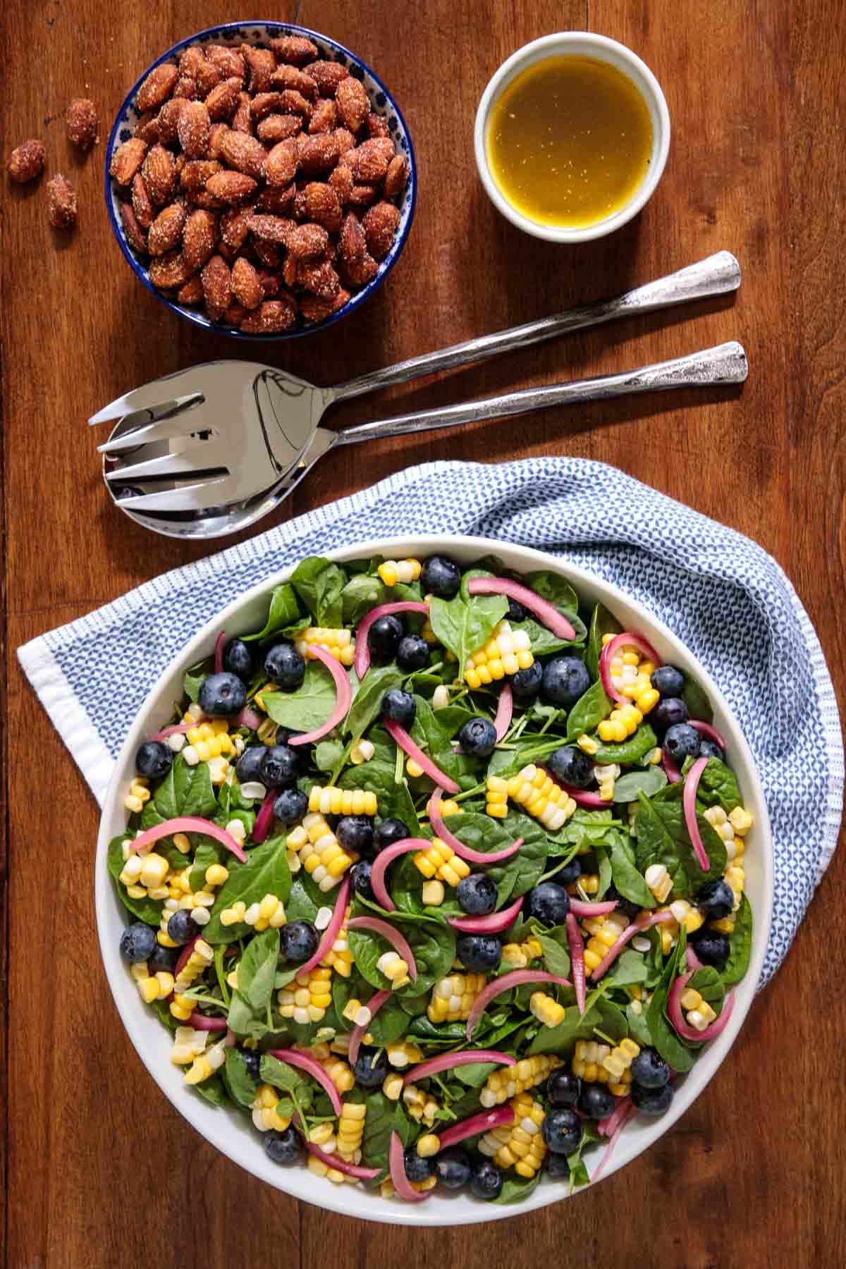 Overhead photo of a salad bowl of Fresh Corn Blueberry Spinach Salad with a bowl of dressing and a bowl of toasted sweet/spicy almonds next to the salad.