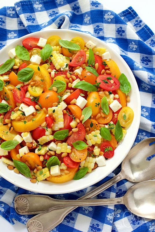 Overhead photo of Fresh Corn and Tomato Caprese Salad in a white bowl on a blue and white checkered cloth.