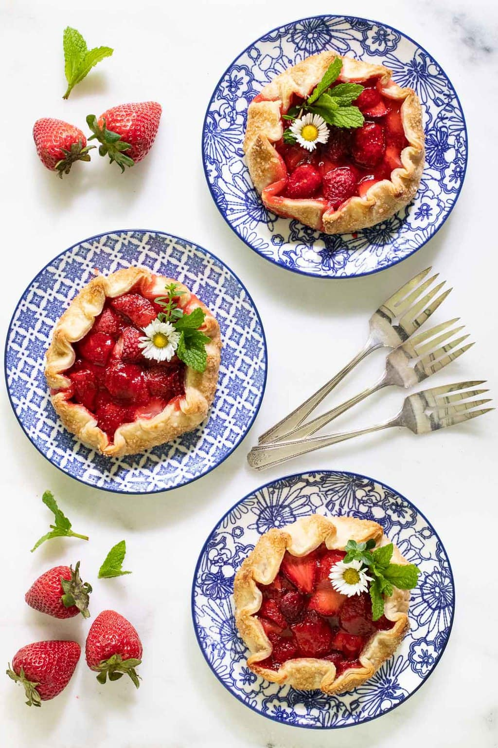 Overhead vertical photo of three serving plate with Fresh Strawberry Galettes on them. They are surrounded by fresh strawberries and garnished with mint leaves.
