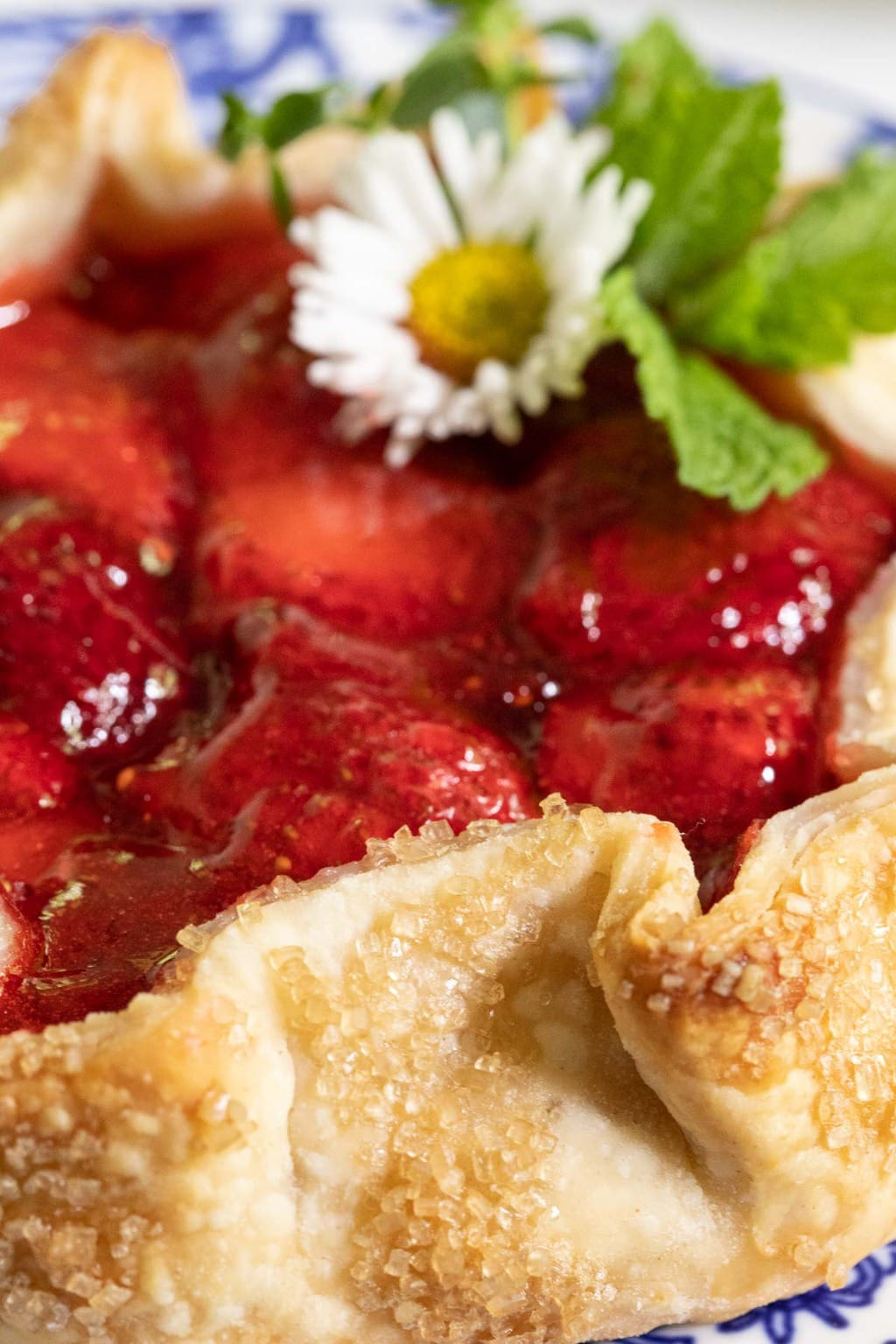Ultra closeup vertical side photo of a Fresh Strawberry Galette garnished with a wild daisy and fresh mint leaves.