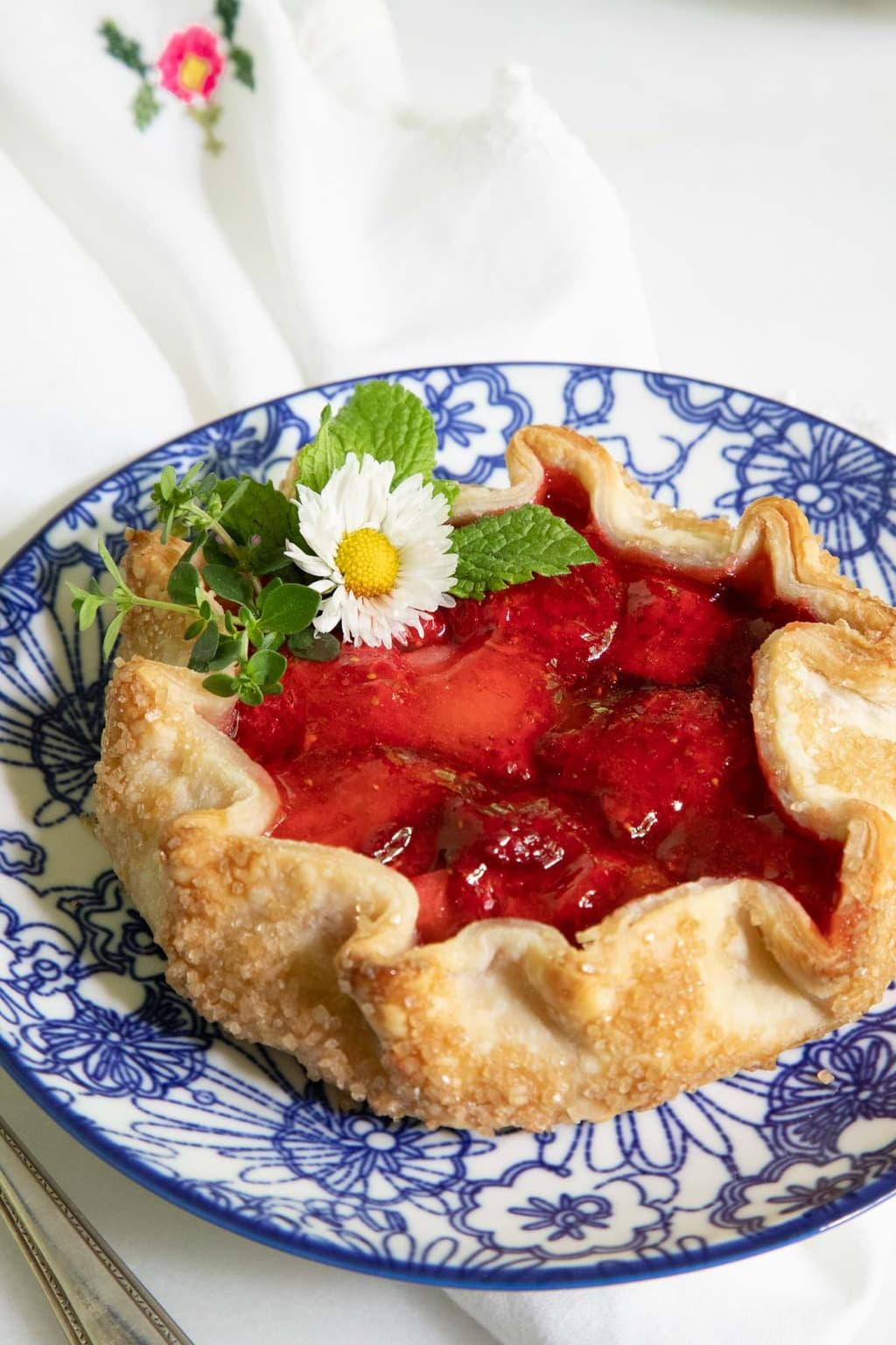 Vertical closeup photo of a Fresh Strawberry Galette on a blue and white patterned plate garnished with a wild daisy and fresh mint leaves.