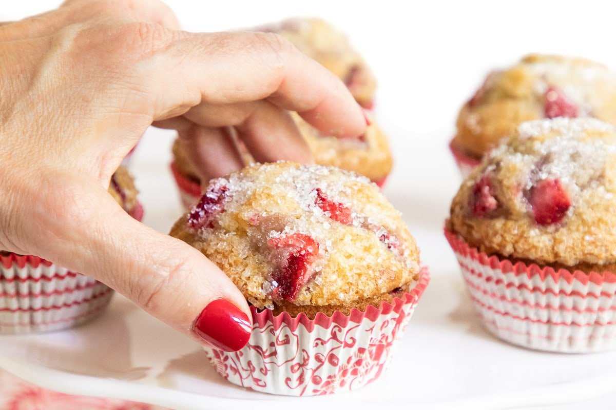 Horizontal closeup photo of Fresh Strawberry Muffins on a white serving platter with a hand grabbing one of the muffins.