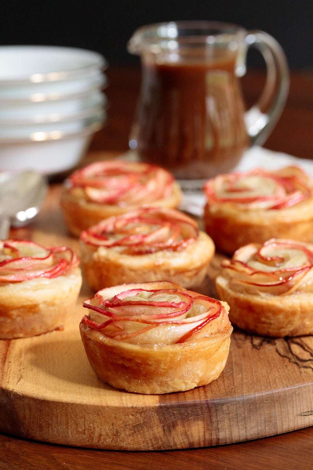 Overall photo of a batch of Glazed Puff Pastry Apple Roses on a wood presentation board with a small pitcher of salted apple caramel sauce.
