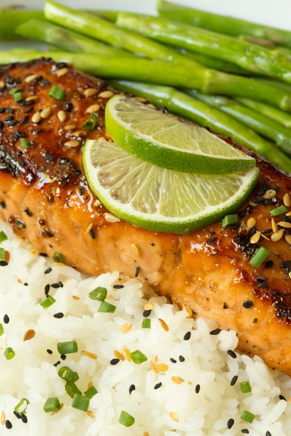 Closeup photo of Honey Bourbon Glazed Salmon on a bed of seasoned white rice, a side of asparagus and garnished with lime wedges.