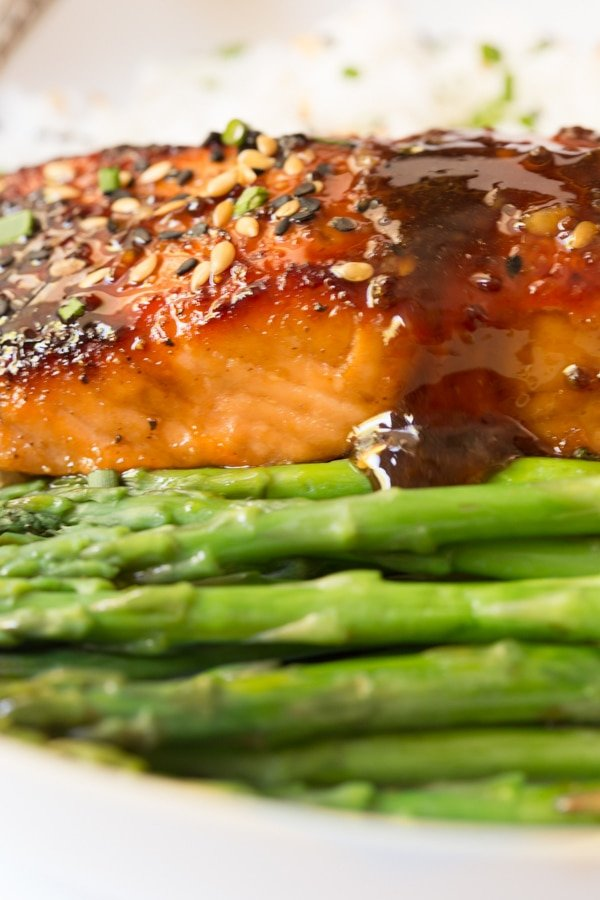 A horizontal photo of Honey Bourbon Glazed Salmon with a side of asparagus in front.