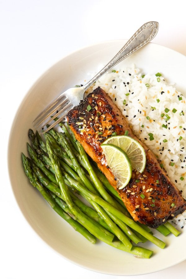 Overhead photo of Honey Bourbon Glazed Salmon in a white dish on a bed of rice with a side of asparagus and garnished with lime wedges.
