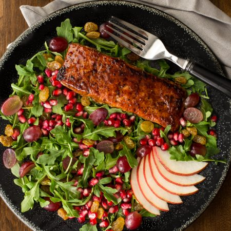 Asian Glazed Salmon Salad with Maple Ginger Dressing For the dressing: ¼ cup rice vinegar 3 tablespoons maple syrup 1 small clove garlic, finely minced 1 tablespoon finely minced fresh ginger 6 tablespoons canola oil 1 teaspoons toasted sesame oil ½ teaspoon kosher salt ¼ teaspoon freshly ground black pepper For the glaze: 2 tablespoons dressing 2 tablespoons low sodium soy sauce 2 tablespoons brown sugar, packed ½ teaspoon black pepper ½ teaspoon sriracha chili sauce* For the salmon: salmon filets, skinless chicken breast halves, cut in bite-size pieces 2 teaspoons brown sugar 1 teaspoon salt ½ teaspoon corn starch 4 4-6-ounce salmon filets, with or without skin 2 teaspoons vegetable oii glaze For the salad: 6-8 cups arugula 1 cup red grapes, halved ½ cup golden raisins* ½ cup pomegranate arils or seeds 1 large or 2 medium red or yellow pear, cored and sliced (leave peel on) 1. For the dressing, combine all ingredients in a glass jar with a tight fitting lid and shake, shake, shake. Set aside. 2. For the glaze, combine all ingredients in a small saucepan and bring to a boil. Reduce to a steady simmer and cook for 3-5 minutes until thickened and syrupy. 3. For the salmon, preheat oven to 300˚F. (150˚C). 4. Combine brown sugar, salt, and cornstarch in small bowl. Pat salmon dry with paper towels and season with a generous sprinkle of freshly ground black pepper. Sprinkle brown sugar mixture evenly over top of flesh side of salmon, rubbing to distribute. (If you're using skinless fillets, rub brown sugar mixture over the nicest looking side of the salmon.) 5. Heat oil in a large, oven-safe nonstick skillet over medium-high heat until hot and just starting to smoke. Place salmon, seasoned side down, in skillet and cook until well browned, about 1-2 minutes. Using tongs, carefully flip salmon and cook on opposite side for 1 minute. 6. Remove skillet from heat and spread a teaspoon of glaze evenly over each salmon fillet. Transfer skillet to oven and cook 7-10 minutes, u